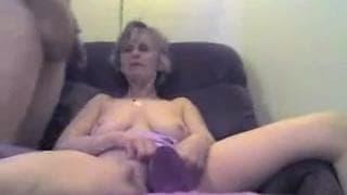 Mulher madura brinca com o dildo na cadeira